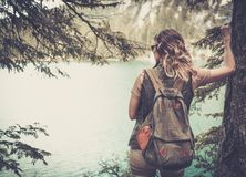 Woman hiker with backpack enjoying amazing mountain lake landscapes. Royalty Free Stock Photos