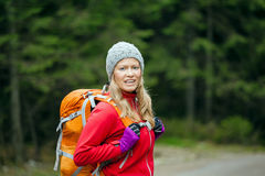 Woman hiker with backpack hiking in forest Stock Image
