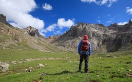 Hiker with backpack hiking at high altitude mountains. Woman hiker with backpack hiking at high altitude mountains Stock Image