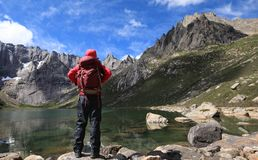 Hiker with backpack hiking at high altitude mountains. Woman hiker with backpack hiking at high altitude mountains Stock Images