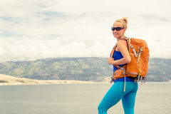 Woman hiker with backpack, hiking at seaside and mountains Stock Images