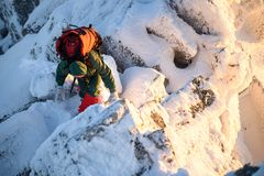 Woman hiker with backpack on the mountain top going thru rocks and snow. Sunset is coming. Woman hiker with backpack on the mountain top going thru rocks and Royalty Free Stock Photo