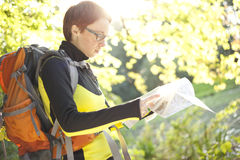 Woman hiker with backpack reading in map in the countryside Stock Images