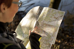 Woman hiker with backpack reading in map in the countryside Royalty Free Stock Photo