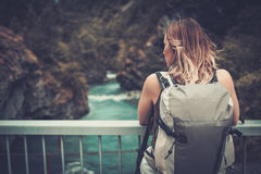Woman hiker with backpack standing on the bridge over a wild mountain river. Royalty Free Stock Photo
