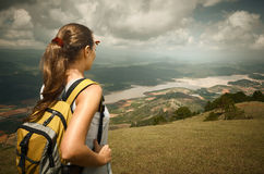 Woman hiker with backpack standing on top of the mountain and en Stock Image