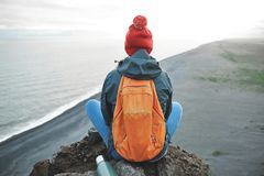 Woman hiker with backpack standing on top of a mountain and enjoying sunset in Iceland. Girl in warm clothing, in red knitted hat and small orange backpack royalty free stock images