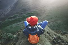 Woman hiker with backpack standing on top of a mountain and enjoying sunset in Iceland. Girl in warm clothing, in red knitted hat and small orange backpack stock photos