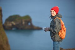 Woman hiker with backpack standing on top of a mountain and enjoying sunset in Iceland. Girl in warm clothing, in red knitted hat and small orange backpack royalty free stock photos