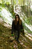 Hiker lady on a trail. Woman hiker with backpack on a trail in the mountains Royalty Free Stock Photography