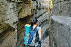 Woman Hiker Backpacker exploring narrow canyon in summer day, view from back Stock Image
