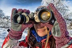 Woman hiker with binoculars. Woman hiker looking into big binoculars. Coarse style picture Stock Photos
