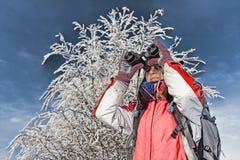 Woman hiker with binoculars. Woman hiker looking into big binoculars. coarse style picture Royalty Free Stock Photo