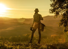 Woman hiker with binoculars enjoying sunset in Tuscany. Discovering magical views of Tuscany. Seen from behind adventure woman hiker in hat with bag and Royalty Free Stock Images