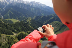 Woman hiker checking the altimeter on sports watch at mountain peak Stock Images