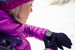 Woman hiker checking sports watch in winter woods and mountains. Woman hiker checking the elevation on sports watch, smartwatch with altimeter app in winter Stock Photography