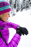 Woman hiker checking sports watch in winter woods and mountains Stock Images