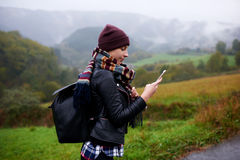 Woman hiker checks weather forecast via cell telephone while climbs the mountain. Young female wanderer using gps navigation on mobile phone to find the right Stock Photos