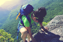 Woman hiker climbing at mountain peak rock Royalty Free Stock Photos