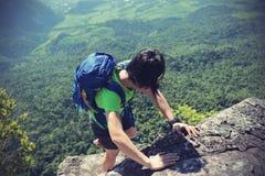 Woman hiker climbing at mountain peak rock Stock Images