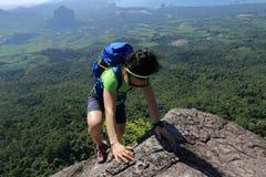 Woman hiker climbing at mountain peak rock Royalty Free Stock Images