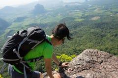 Woman hiker climbing rock on mountain peak cliff. Successful woman hiker climbing rock on mountain peak cliff Stock Photo