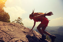 Woman hiker climbing rock on mountain peak cliff Stock Images