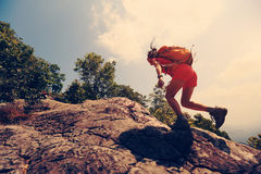 Woman hiker climbing rock on mountain peak cliff Stock Photo