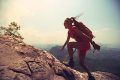 Woman hiker climbing rock on mountain peak cliff Stock Photo