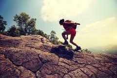 Woman hiker climbing rock on mountain peak cliff Stock Images