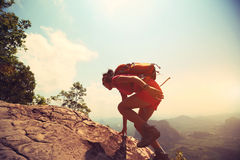 Woman hiker climbing rock on mountain peak cliff Royalty Free Stock Images
