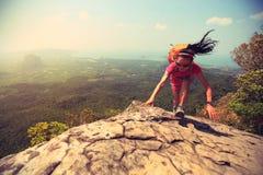 Woman hiker climbing rock on mountain peak cliff Stock Photos