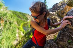 Woman hiker. Climbs the rocky cliff royalty free stock photography