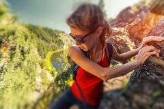 Woman hiker. Climbs the rocky cliff. Tilt shift effect applied royalty free stock photo