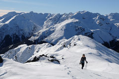 A Woman Hiker Climbs a Snowy Mountain on a Sunny Day. Royalty Free Stock Photography