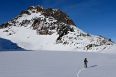A Woman Hiker Crosses a Frozen Lake Towards a Del Campo Peak. Royalty Free Stock Photography