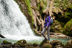 Woman hiker crossing the river Stock Images