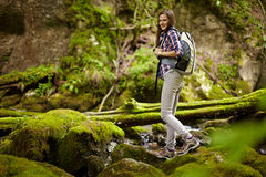 Woman hiker crossing the river Stock Photos