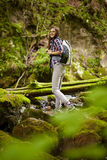 Woman hiker crossing the river Stock Image