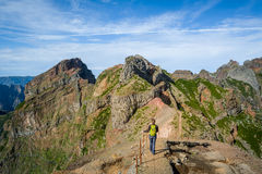 Woman hiker on the dangerous path between the rocky cliffs of Pico Arieiro. Stock Photo