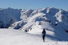 A Woman Hiker Descends a High and Snowy Peak with Mountain Views Beyond Royalty Free Stock Image