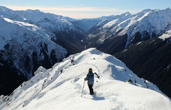 A Woman Hiker Descends a Snowy Peak with Mountain Views and River Canyon Beyond. Stock Photos