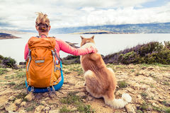 Woman hiker with dog looking at sea Royalty Free Stock Images