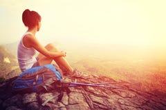 Woman hiker enjoy the view at mountain peak cliff. Woman hiker enjoy the view sitting at sunset mountain peak cliff Stock Photo