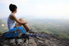 Woman hiker enjoy the view at mountain peak cliff. Woman hiker enjoy the view sitting at sunset mountain peak cliff Stock Image