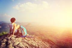 Woman hiker enjoy the view at mountain peak cliff. Woman hiker enjoy the view sitting at sunset mountain peak cliff Royalty Free Stock Images