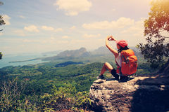 Woman hiker enjoy the view on mountain top cliff Royalty Free Stock Images