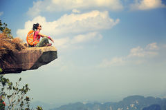 Woman hiker enjoy the view on mountain top cliff Stock Image