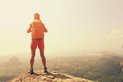 Woman hiker enjoy the view on mountain top rock Stock Photos