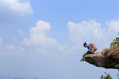 Woman hiker enjoy the view on mountain top rock Stock Photo
